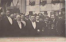 el 1911, venas el serio de fotaj poŝtkartoj, kiuj dokumentis okazintaĵojn de la 7-a UK en Antverpeno. Ĝi montras Zamenhof kaj d-ron van der Biest-Andelhof, prezidanto de la kongreso, apud antverpena policisto.
